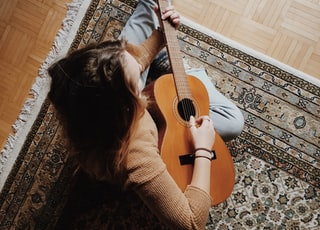 person playing guitar while sitting on area rug