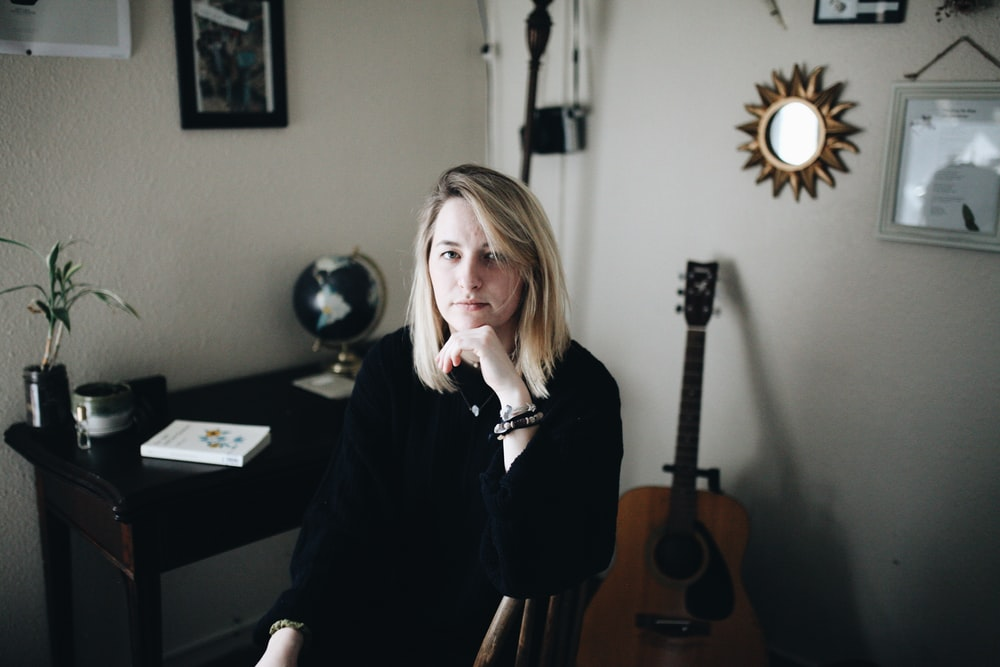 woman seated near desk hand on cheek