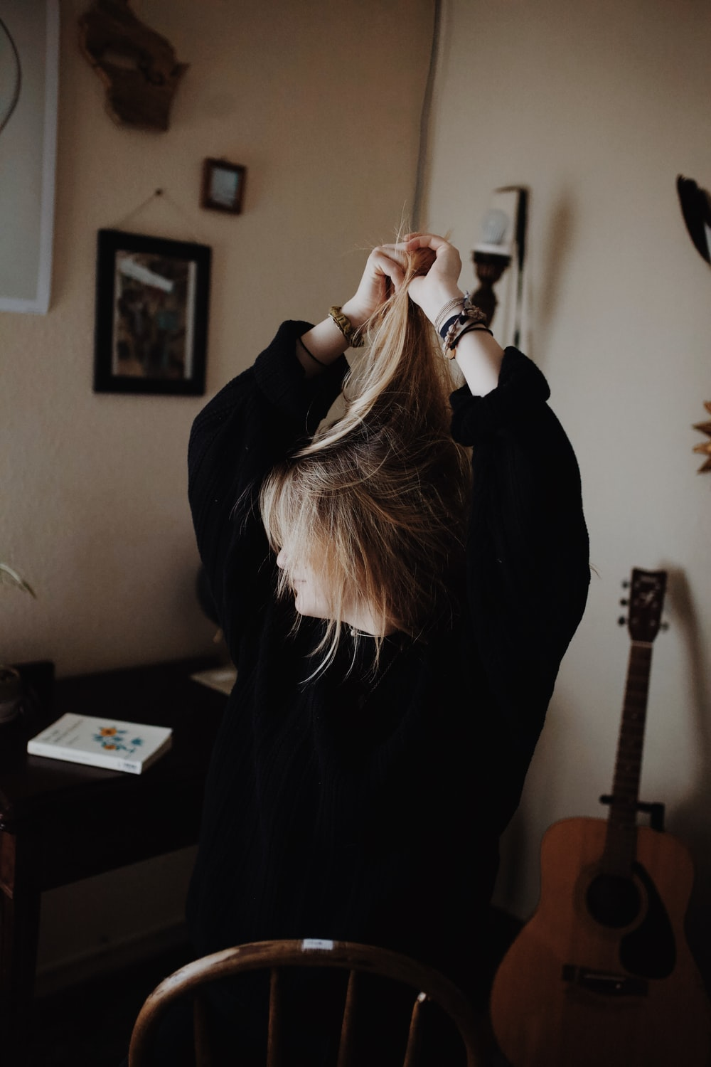 woman in black sweater holding her hair