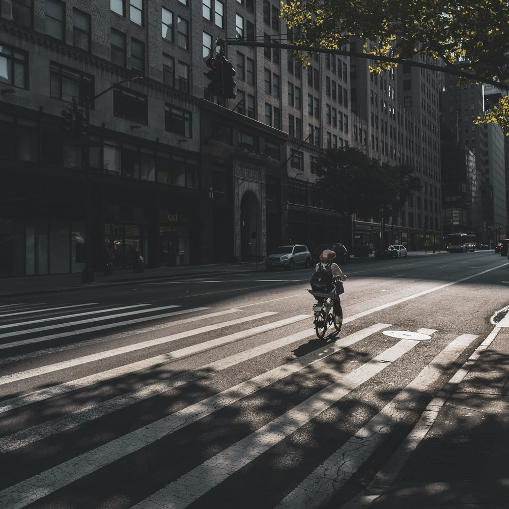 person riding on bicycle near buildings