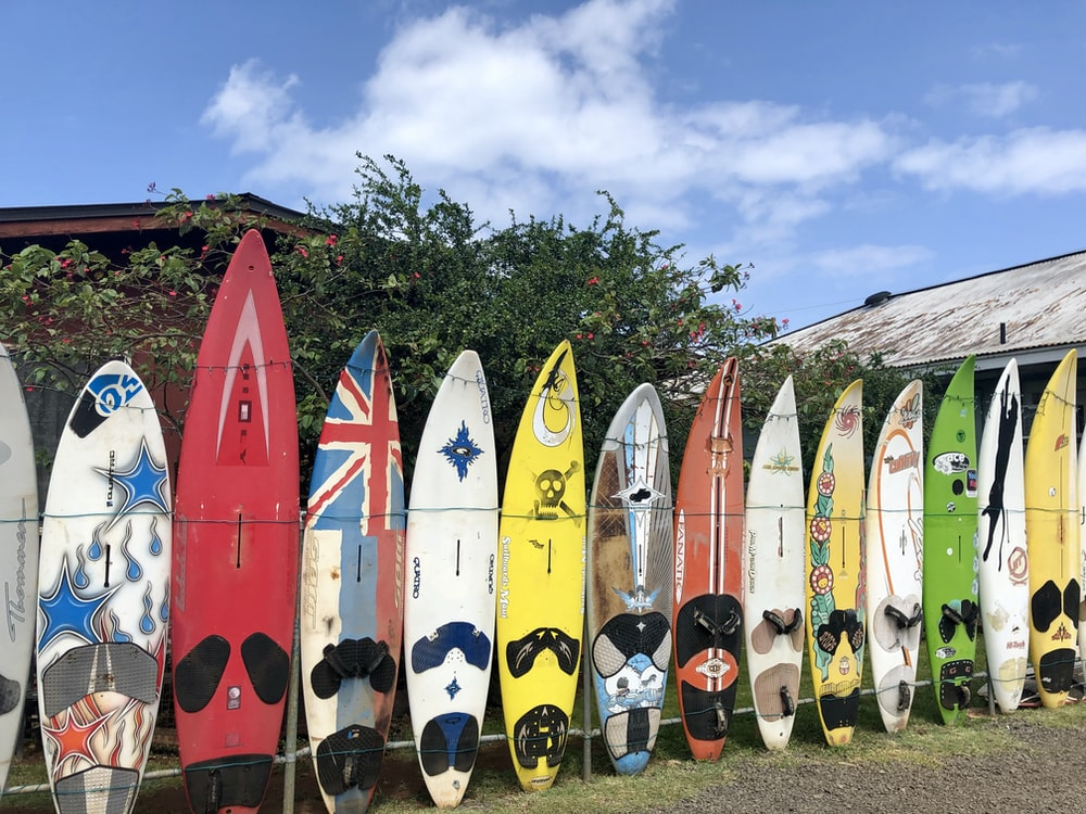 assorted-color surfboard standing under white and blue sky