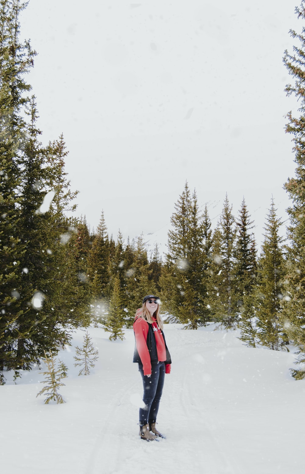 woman in red top and black jeans on snow field