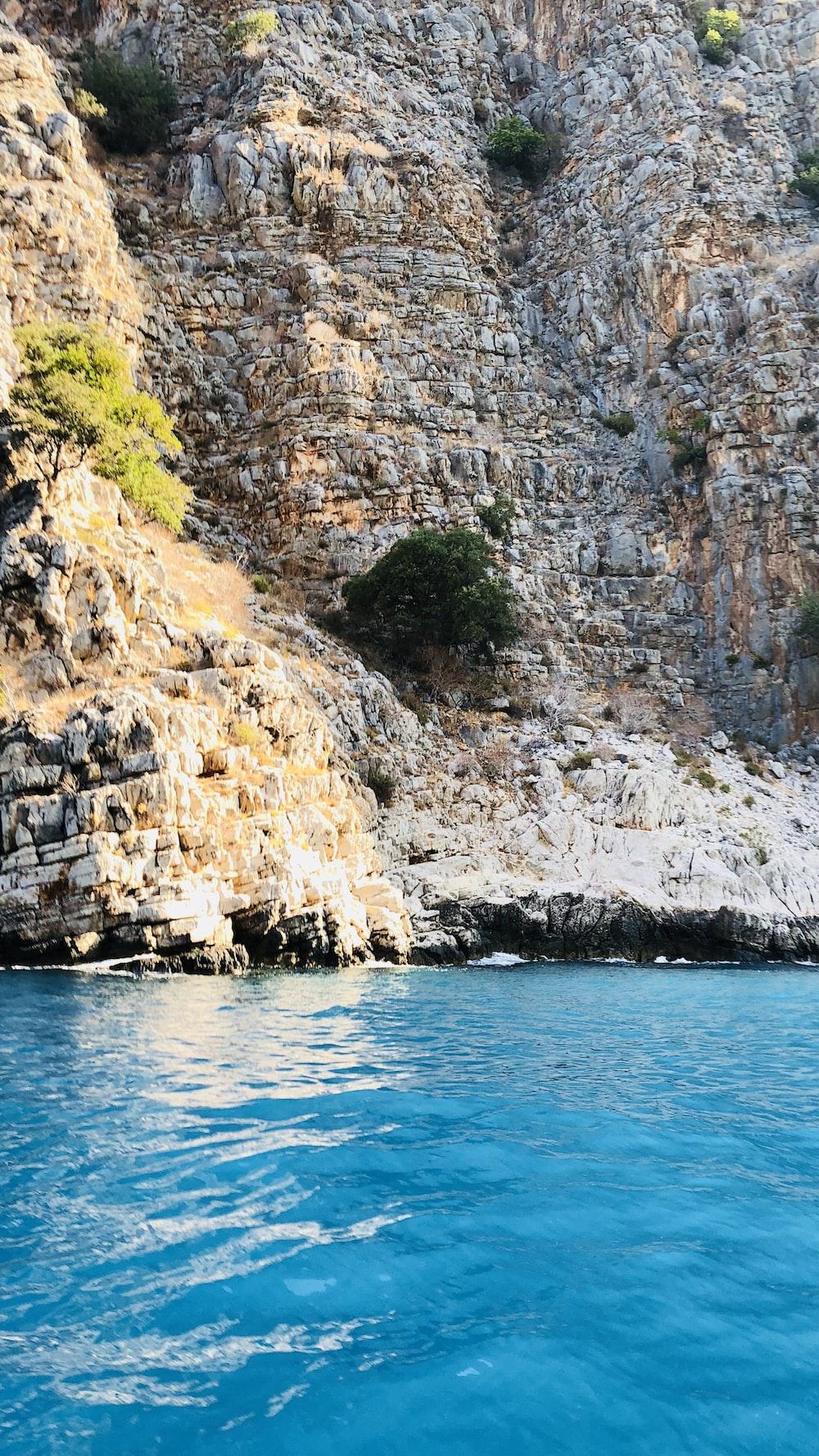 calm body of water near cliffs
