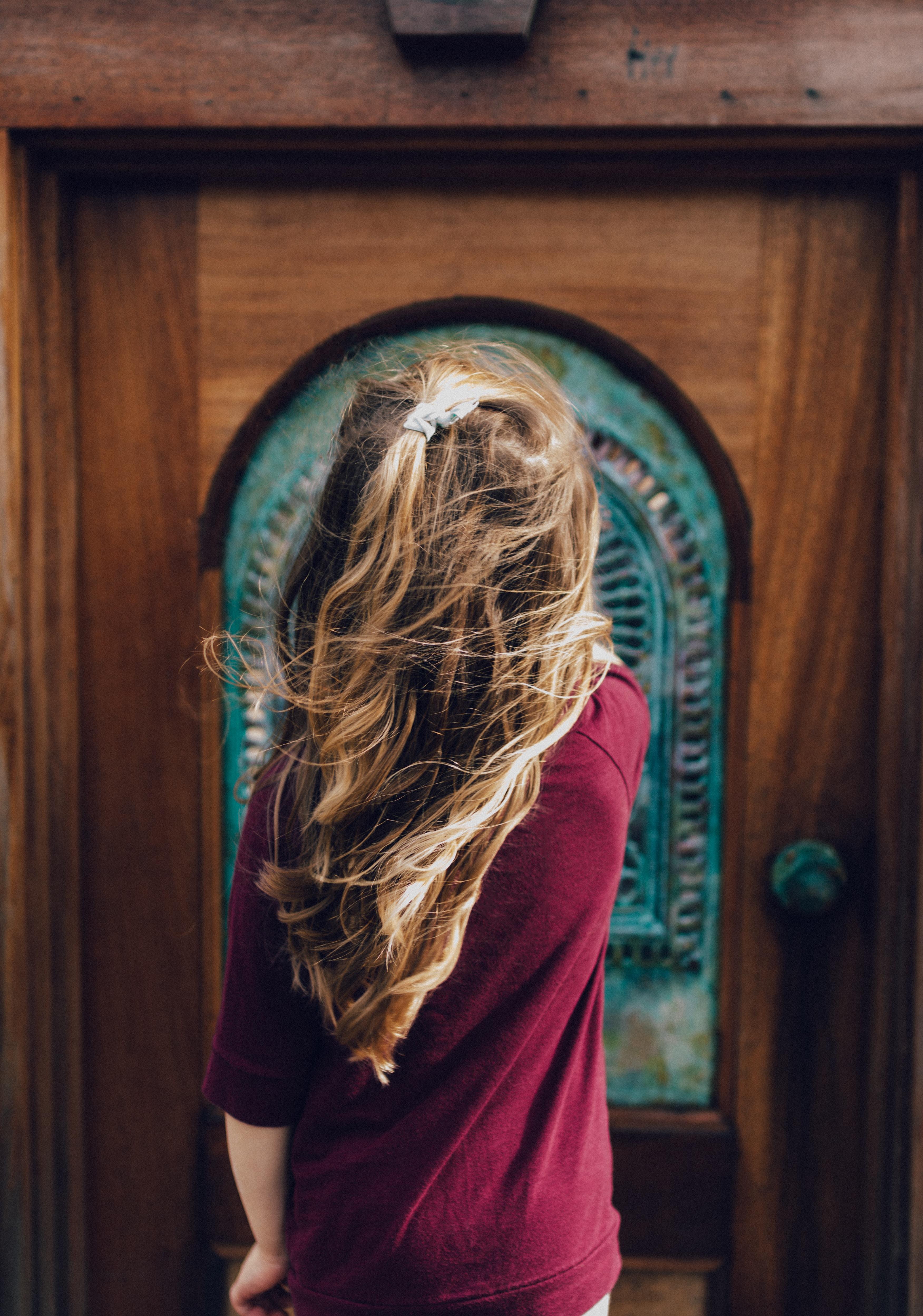 man wearing red sweater in front of door