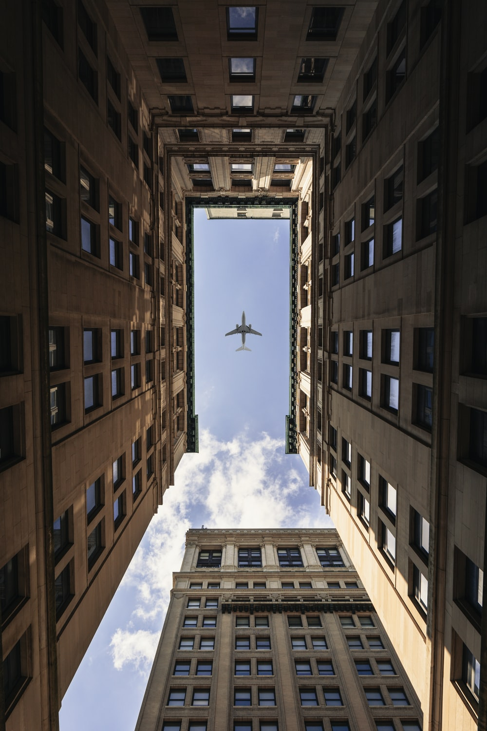 airplane flying on top of high rise buildings