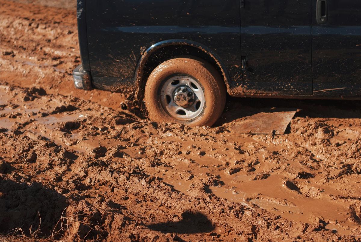 Tire of a navy blue cargo van stuck in red mud.