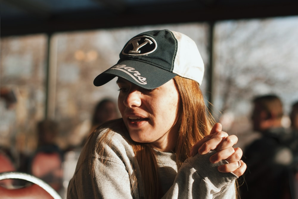 woman wearing grey sweater and cap looking side