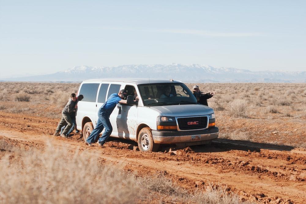 men pushing white GMC van