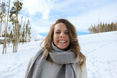 woman wearing gray scarf standing snow and smiling during daytime scarf teams background
