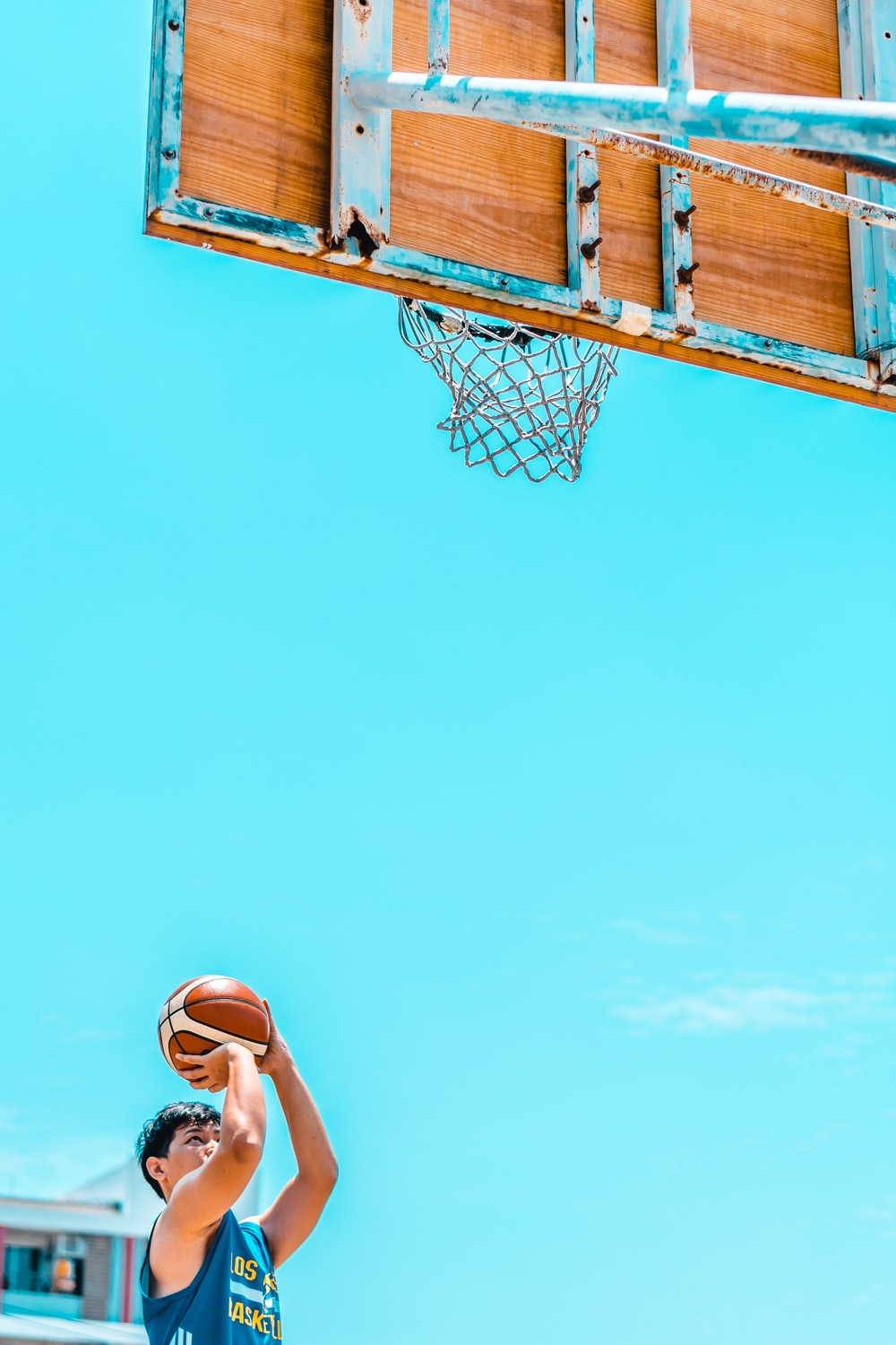 man holding basketball in front of basketball system during daytime