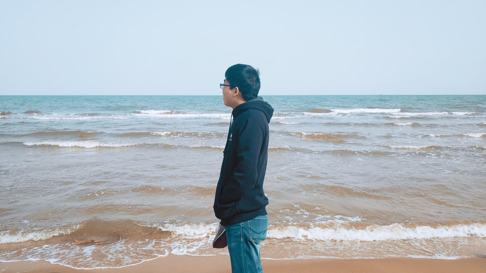 man in black hoodie standing on shore