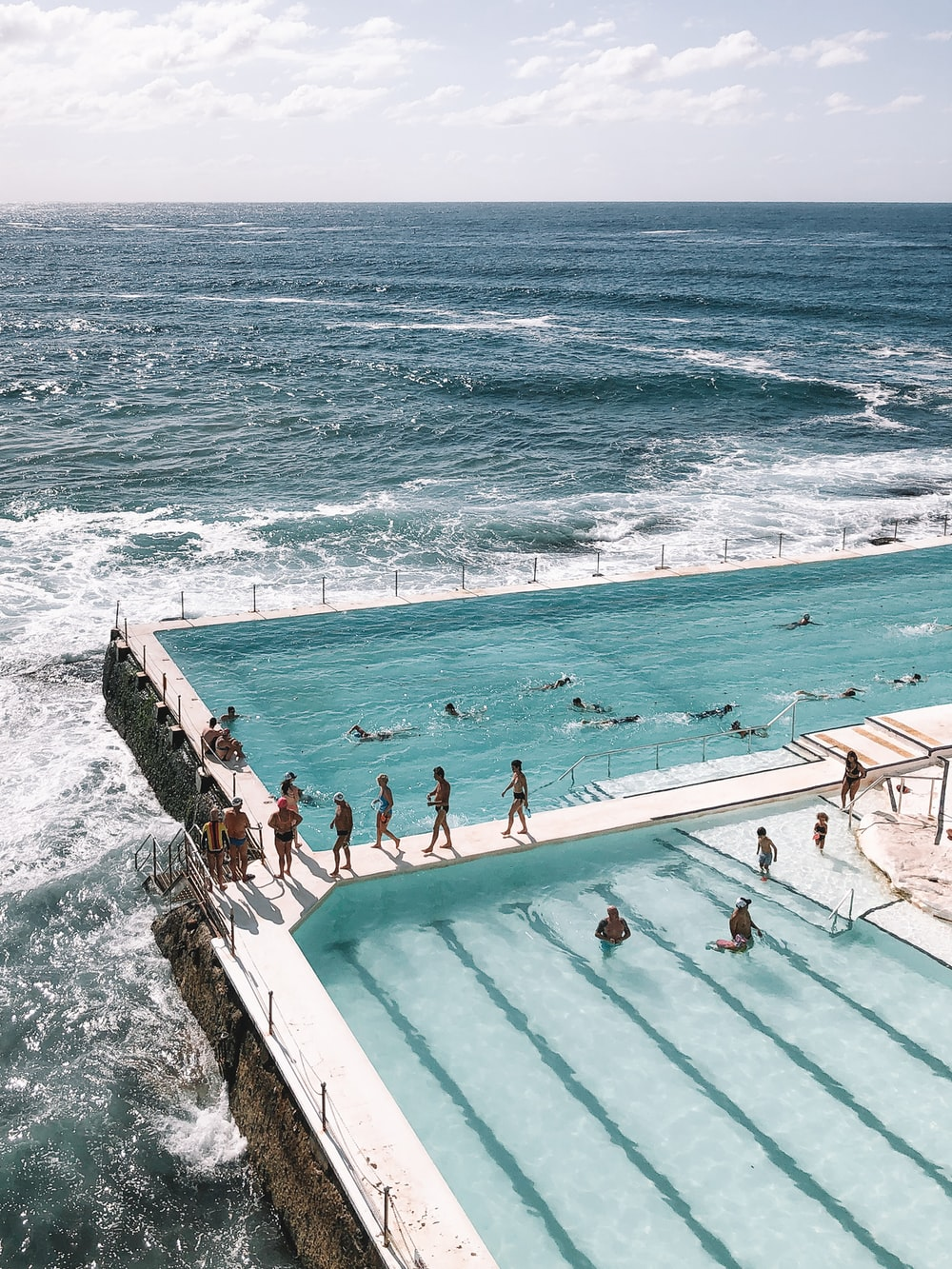 people swimming on pool near sea