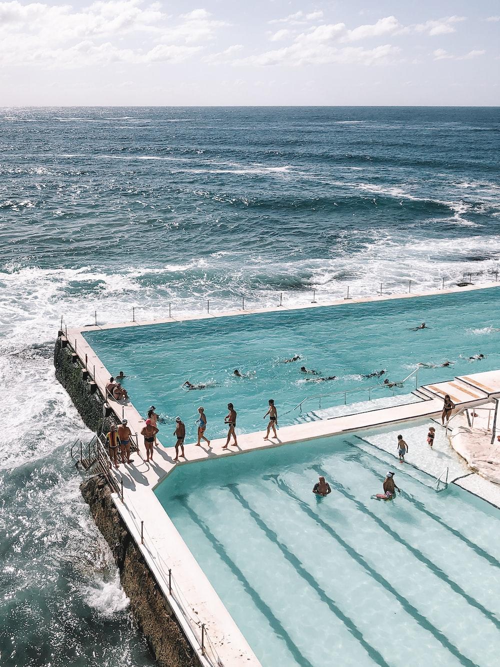 people swimming on pool near sea