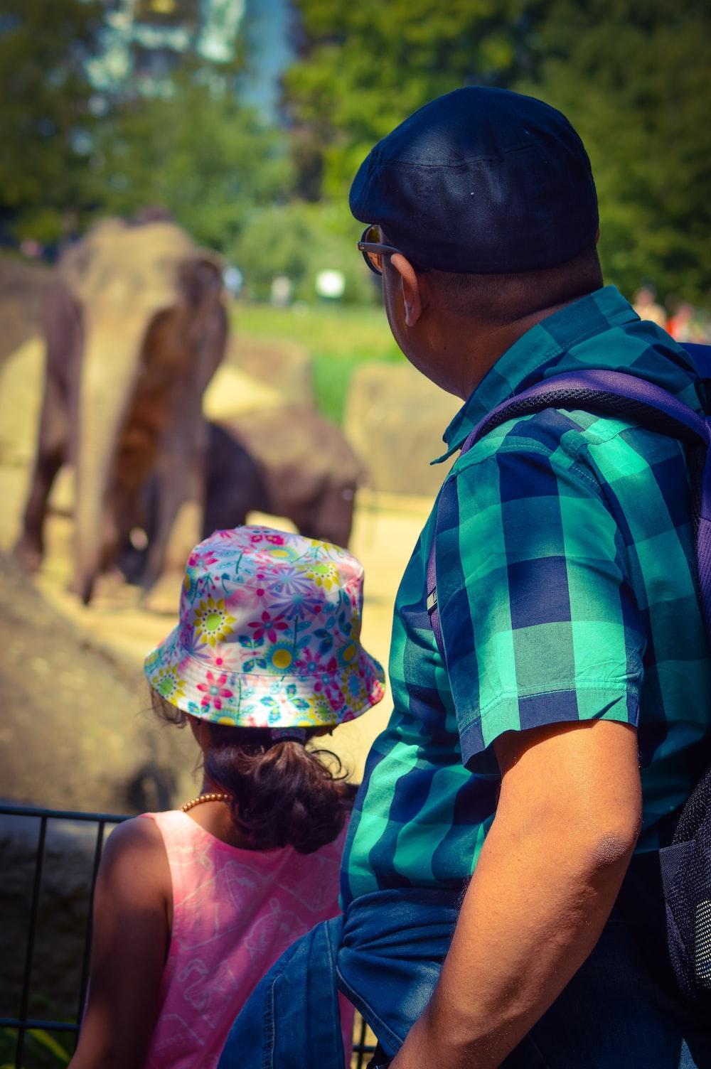 man wearing blue checked shirt standing near girl staring at elephants