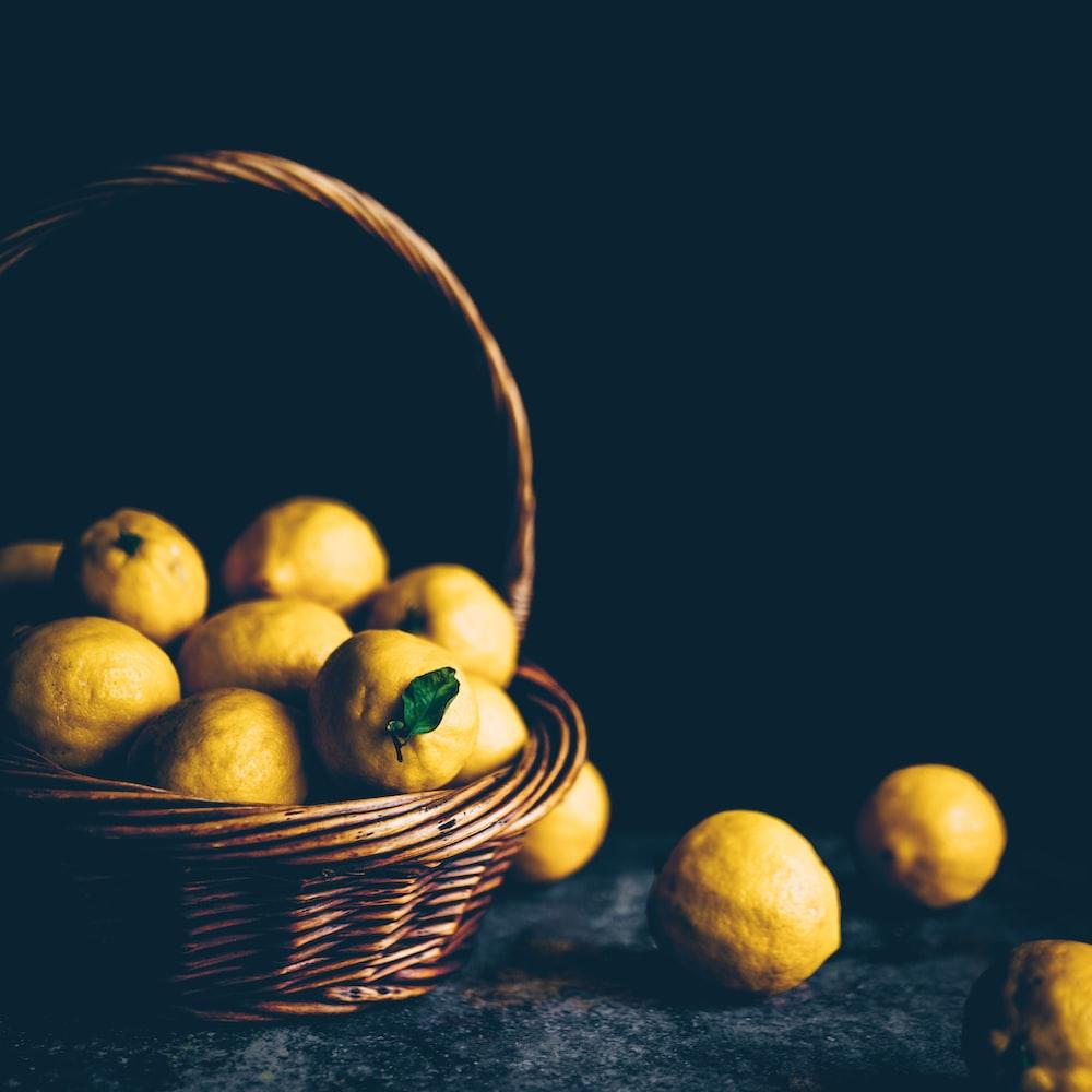 yellow lemons on brown wicker basket