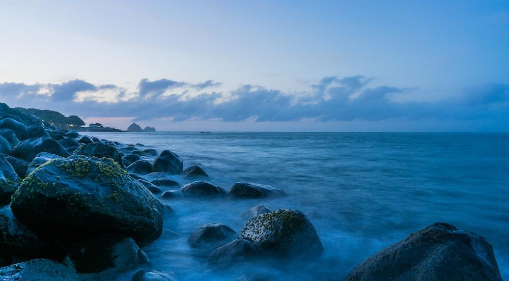 rocks near calm sea under blue sky