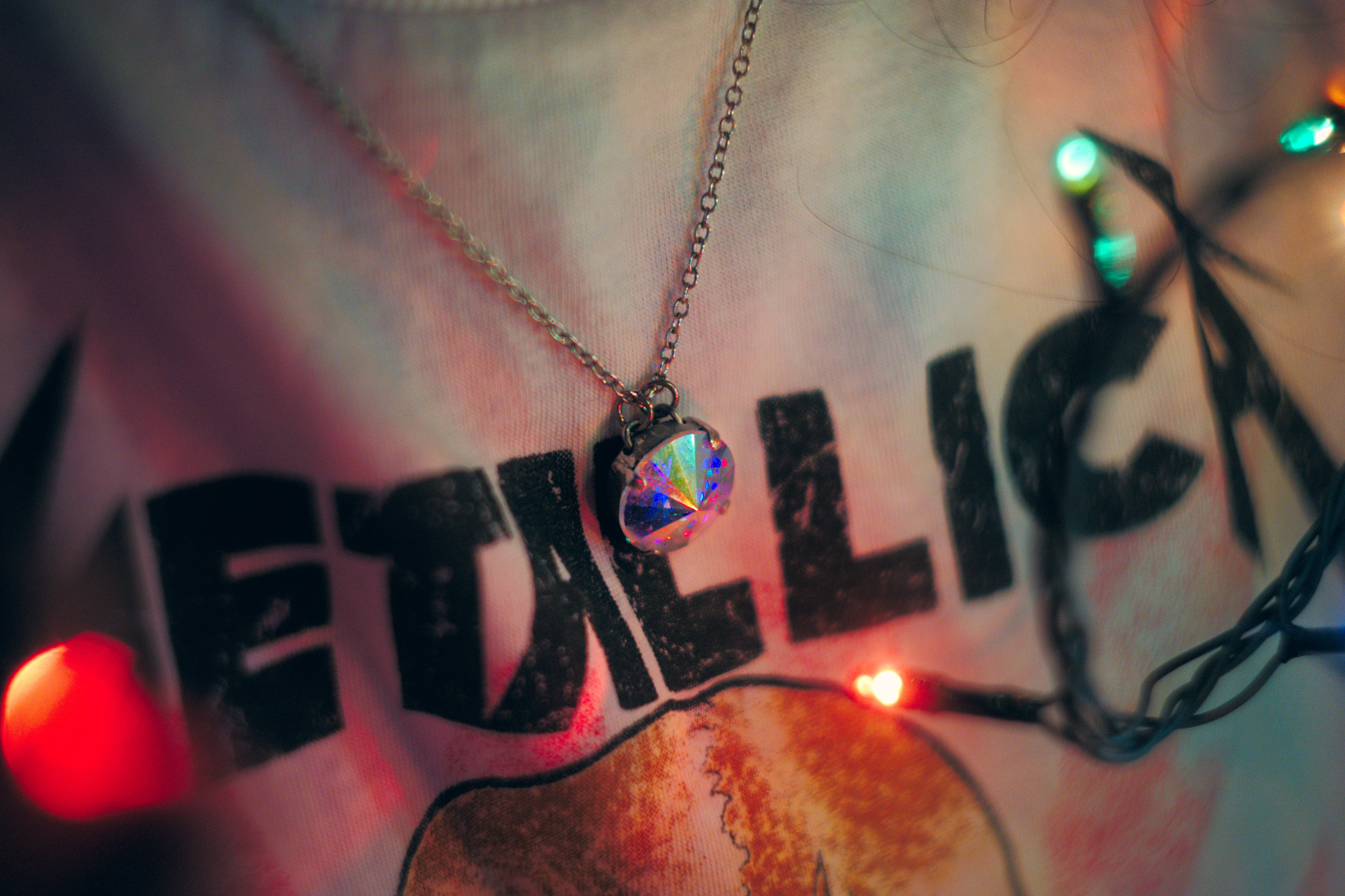 Metallica-prinetd shirt and iridescent pendant necklace