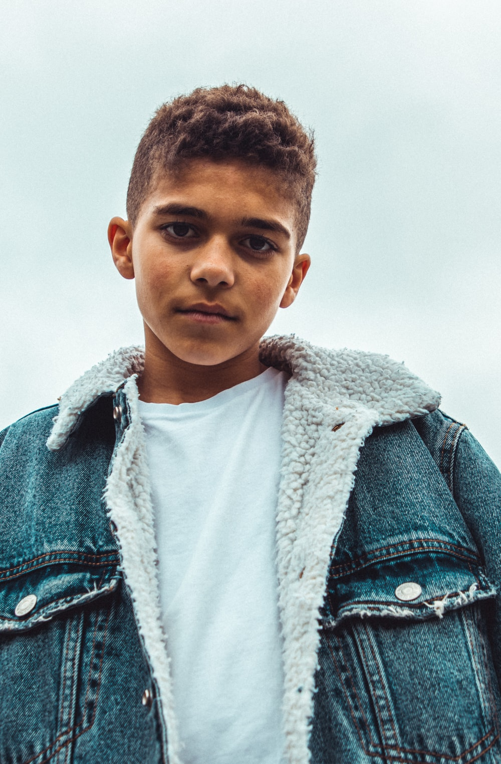 boy wearing blue denim jacket standing and looking straight