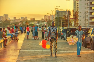 person in white and black shirt holding balloons while standing near person holding food packs during golden hour mozambique zoom background