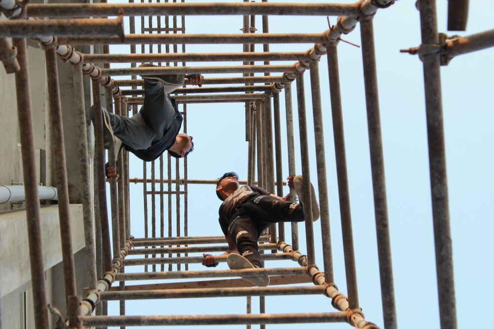 two men on brown metal pipes