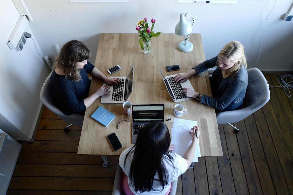 three women sitting around table using laptops