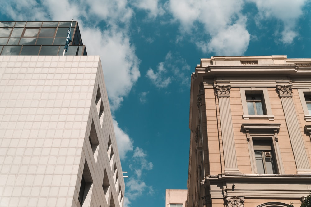 white cloudy blue sky over two high rise buildings