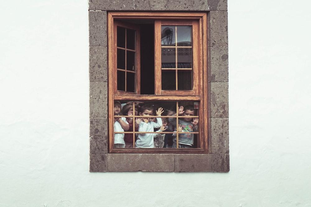 kids behind the window of building