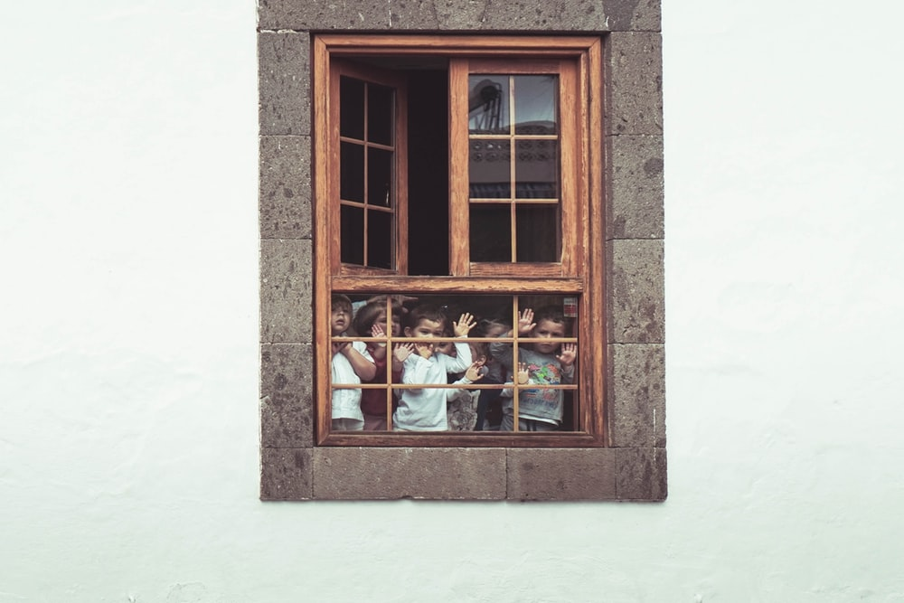 kids behind the window of building