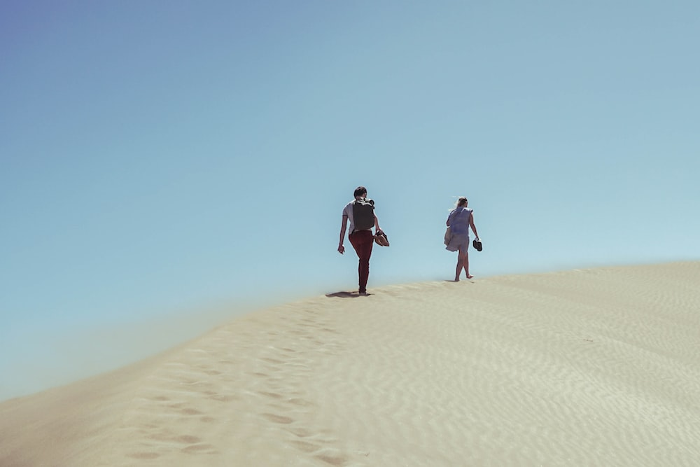 two persons walking on desert during daytime