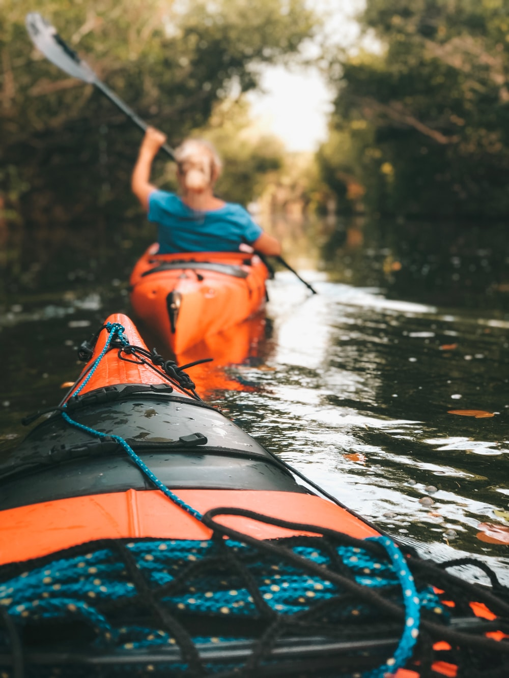 selective focus photography of woman riding kayak holding oar during daytime