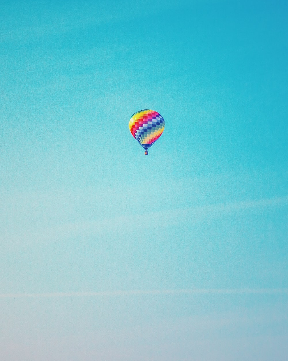 multicolored hot air balloon under clear blue sky