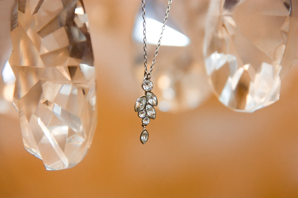 silver-colored diamond pendant necklace