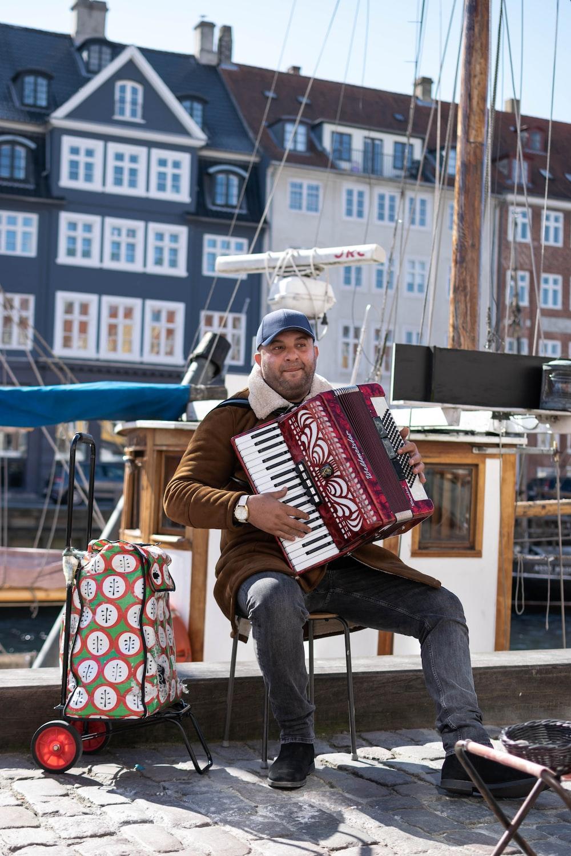 man sitting on chair playing harmonium