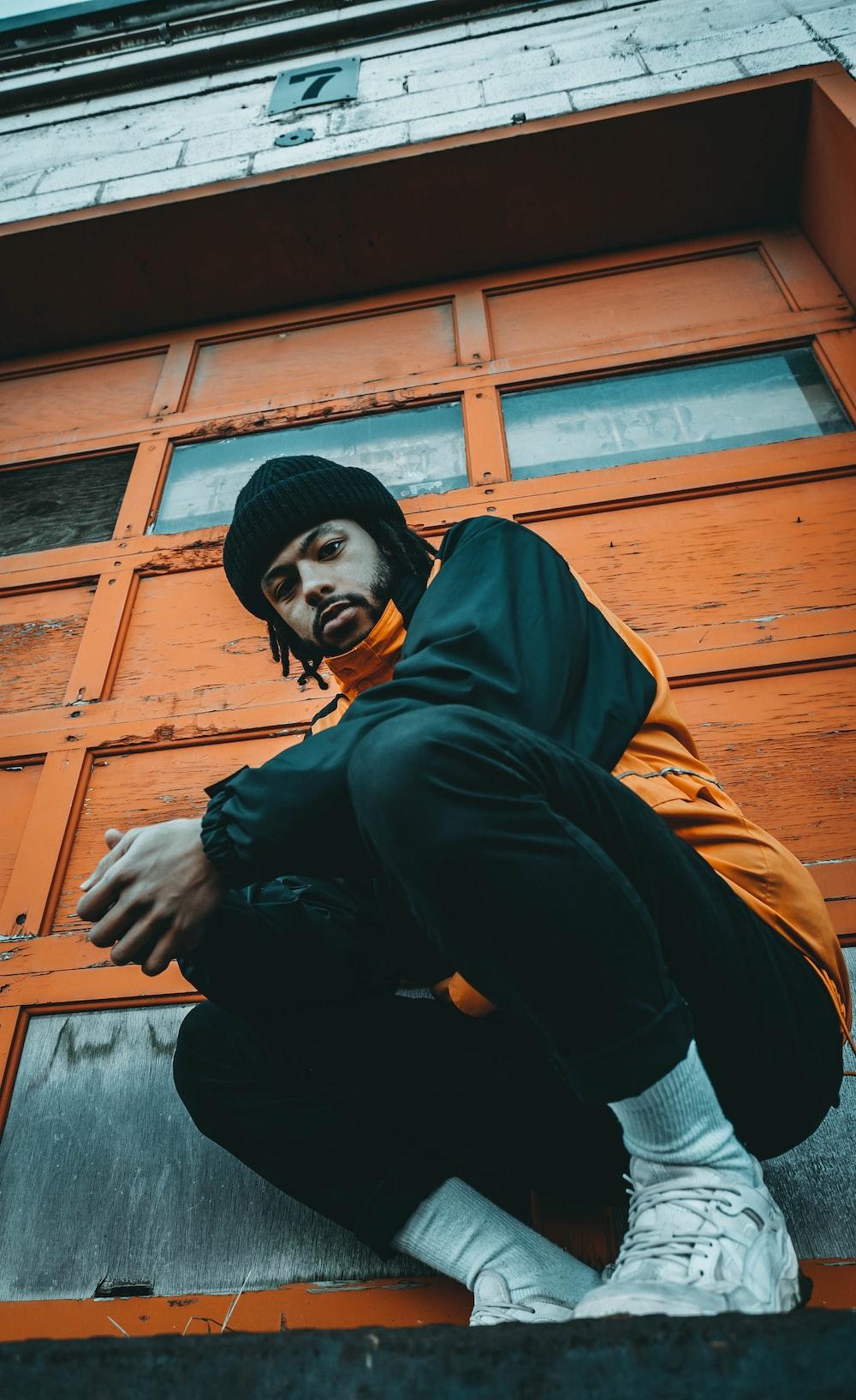 crouching man wearing black and orange jacket beside wall