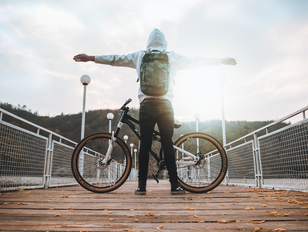 man standing in front of black hardtail bicycle