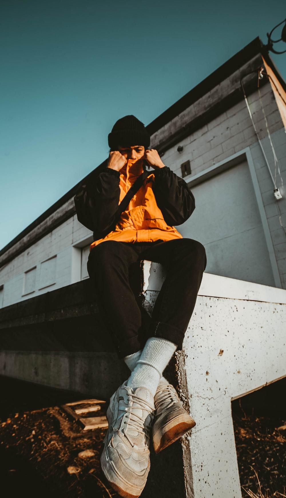 man wearing orange and black jacket