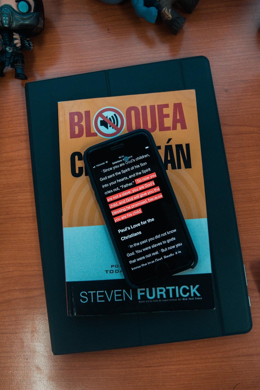 black smartphone on top of Steven Furtick book