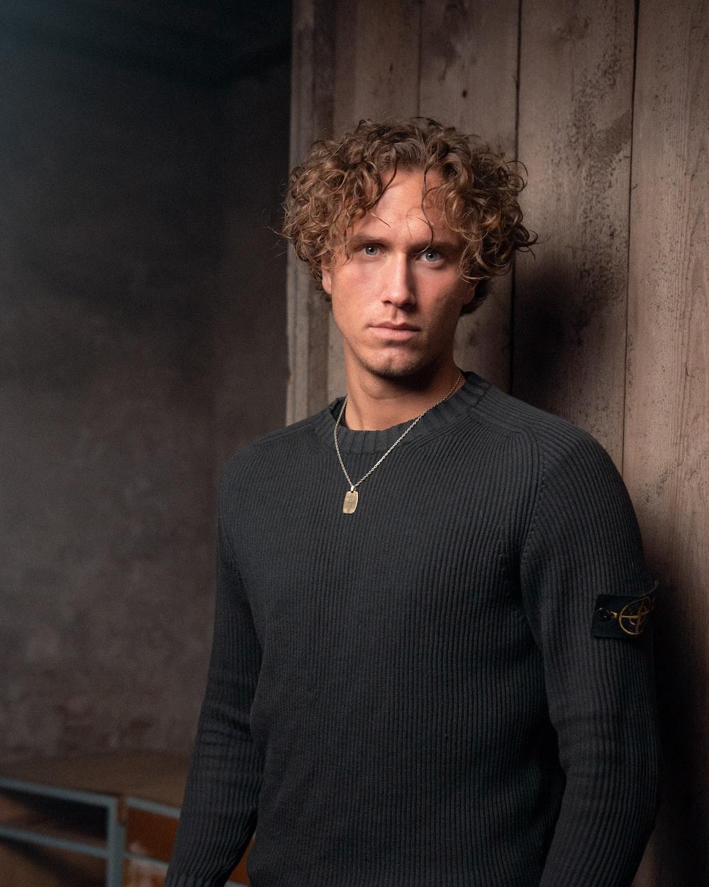 man wearing black knit sweater standing near brown wall