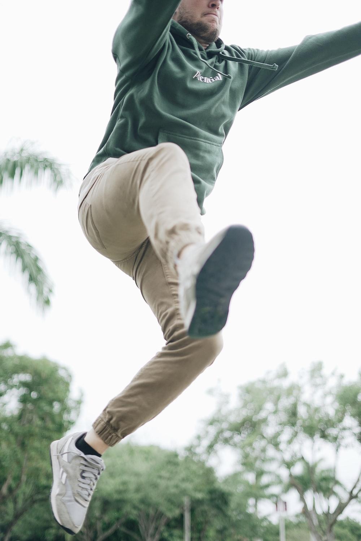 man jumping near tree