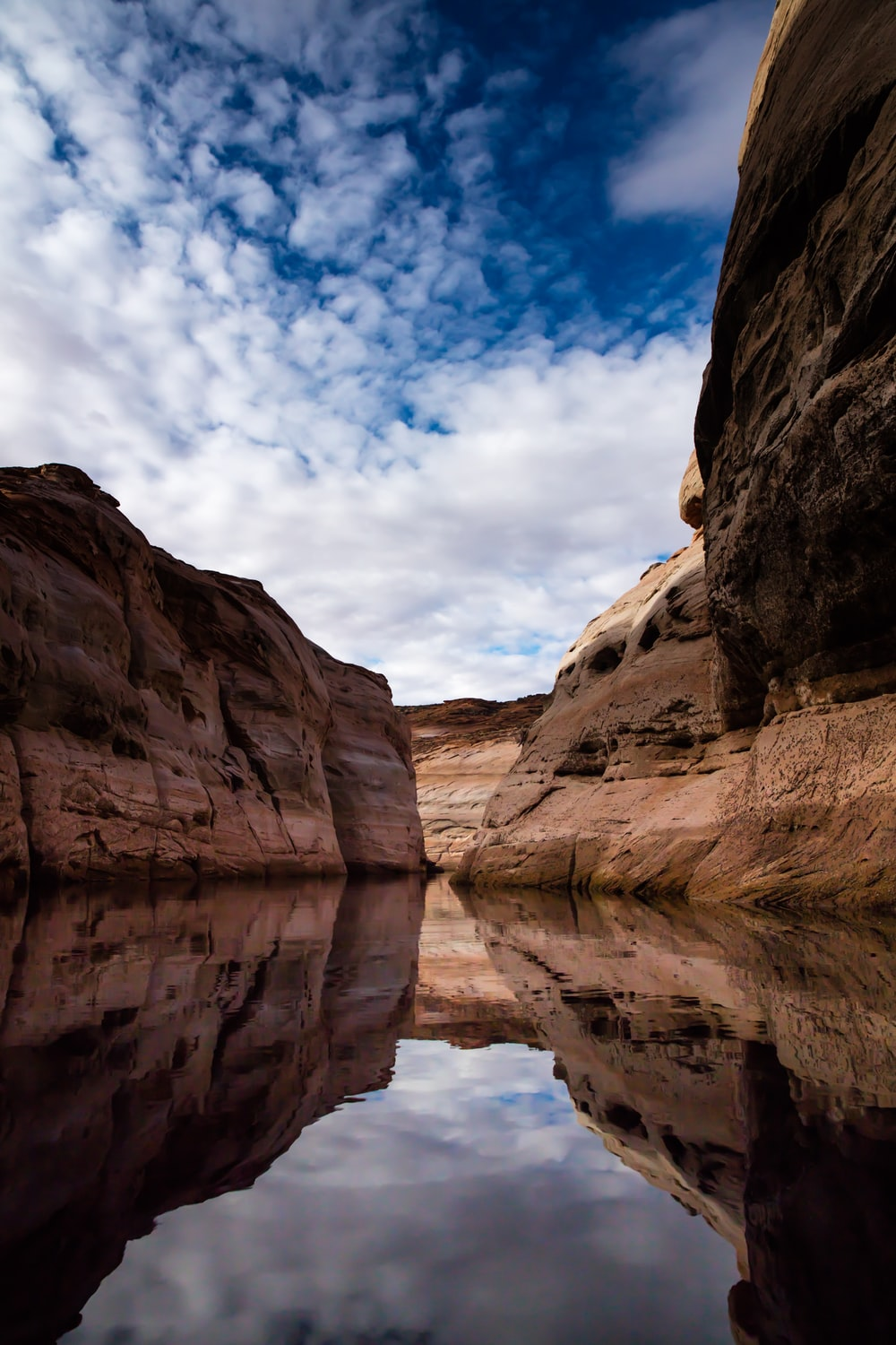 reflections of brown rocks on calm body of water