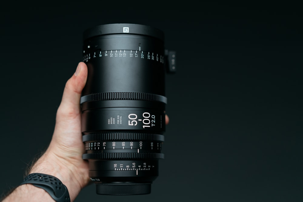 person holding 50-100 mm T2.0 camera zoom lens