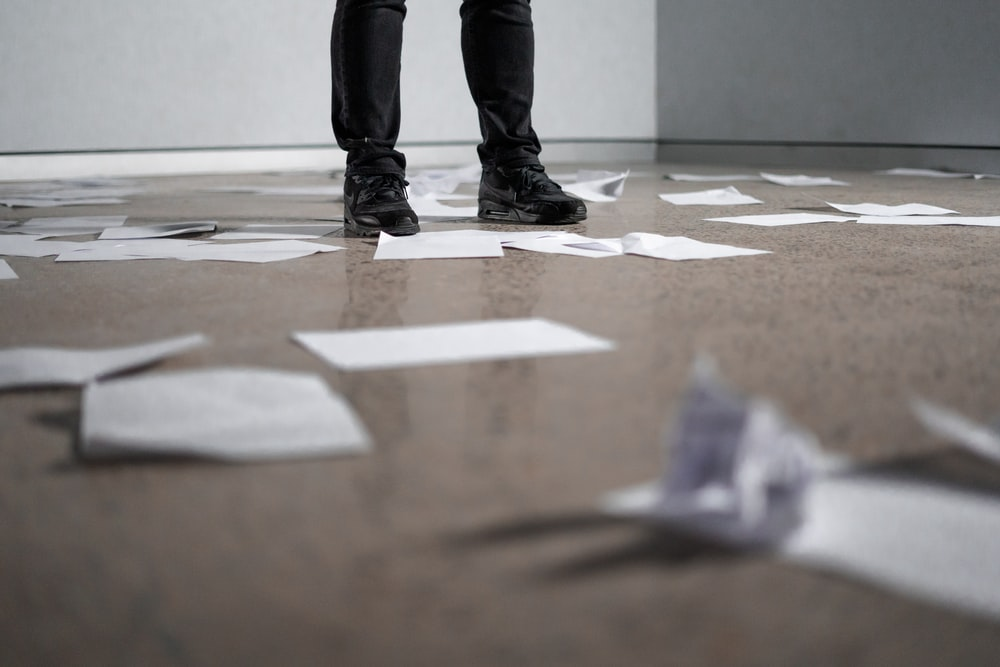 person standing near papers on ground