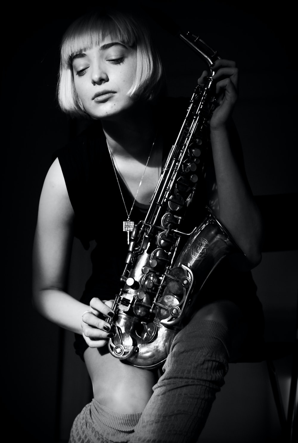grayscale photography of woman holding saxophone
