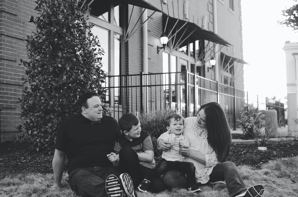 grayscale photography of family sitting beside tree