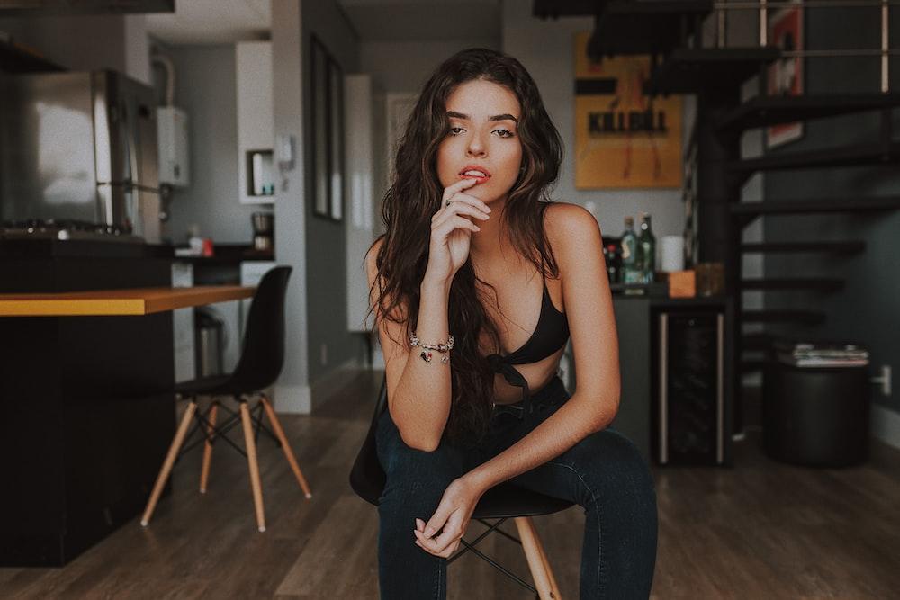 woman in black bikini top and blue denim jeans sitting on stool