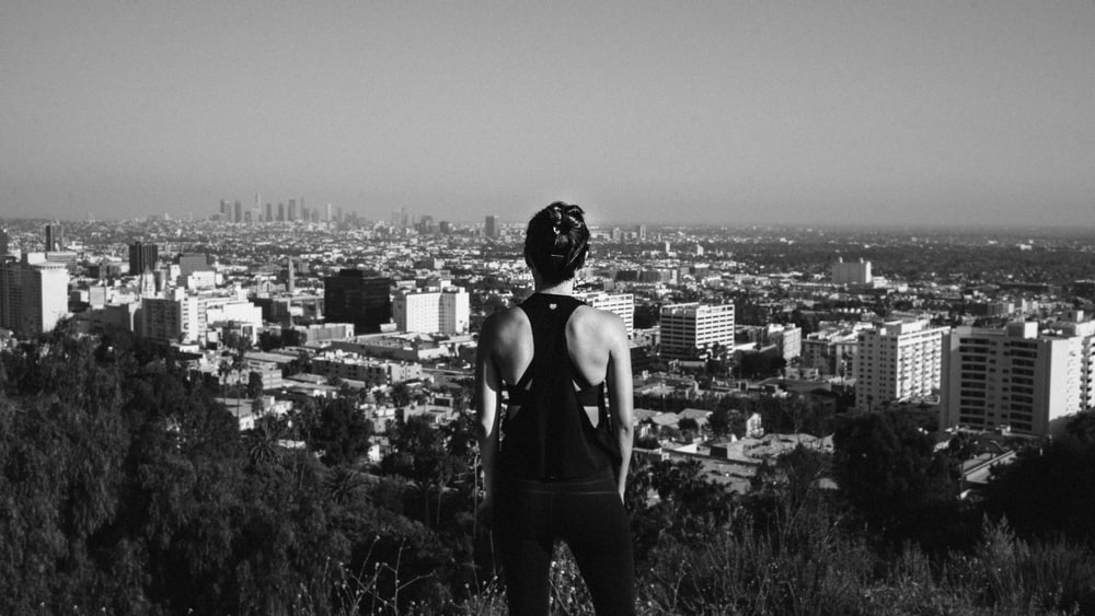 grayscale photography of woman standing near high buildings