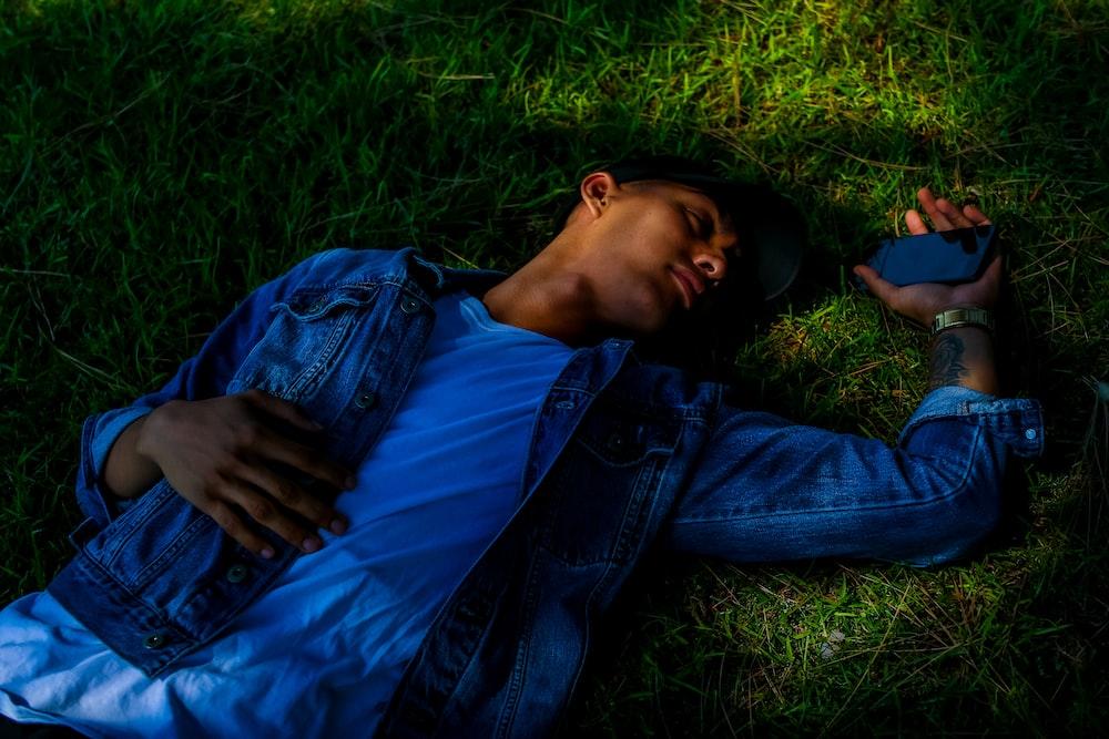 man lying on grass holding smartphone