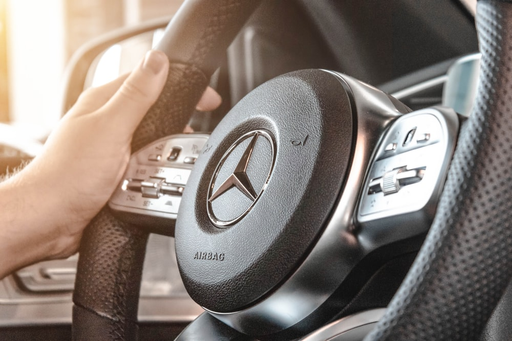 person holding Mercedes-Benz multifunction steering wheel