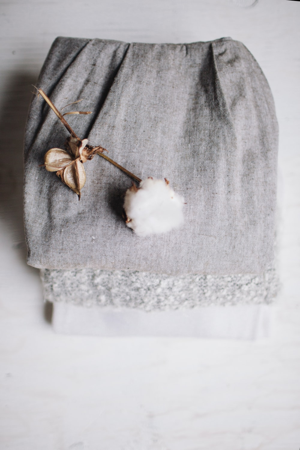 white cotton poppy on top of grey textile