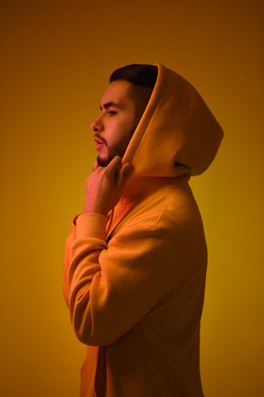 man wearing yellow pullover hoodie